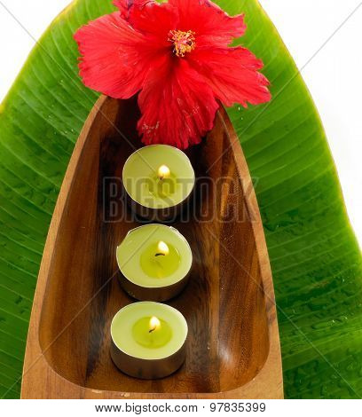 Red hibiscus with candle in wooden bowl on banana leaf