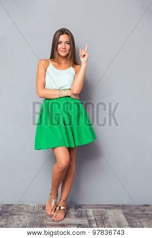 Full length portrait of a pretty girl pointing finger up and looking at camera over gray background