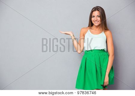 Smiling pretty girl holding copyspace on the palm over gray background