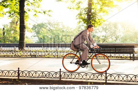 Handsome businessman riding bicycle to work in park