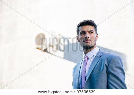 Portrait of a handsome thoughtful businessman standing outdoors