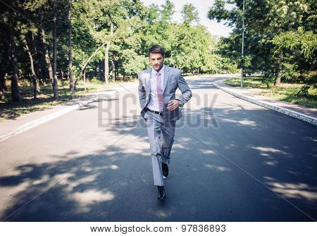 Handsome businessman in suit running in park