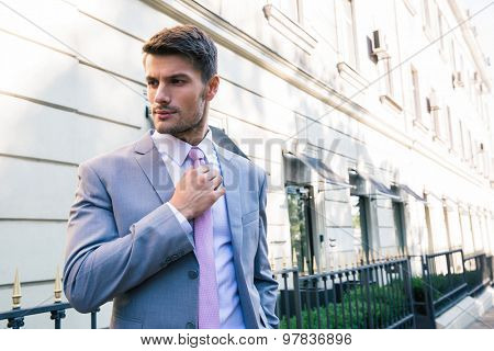 Confident businessman straightens his tie outdoors