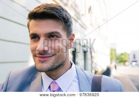 Portrait of a happy businessman outdoors looking away