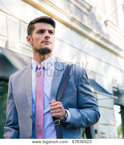 Portrait of a confident young businessman walking outdoors in town