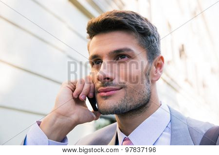Portrait of a happy businessman talking on the phone in the city
