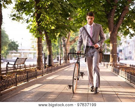 Pensive young businessman walking with bicycle on the street in town