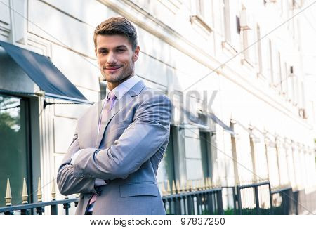 Handsome businessman standing with arms folded outdoors in town