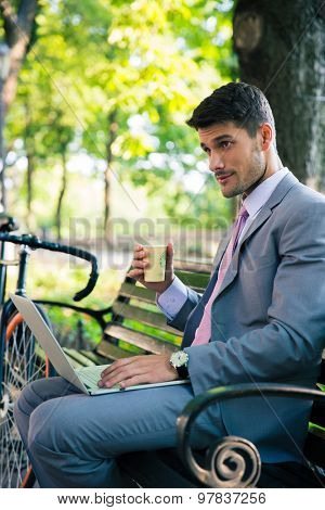 Portrait of a handsome businessman sitting on the bench with laptop and drinking coffee outdoors