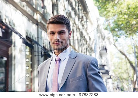 Portrait of a handsome businessman in suit standing outdoors and looking at camera
