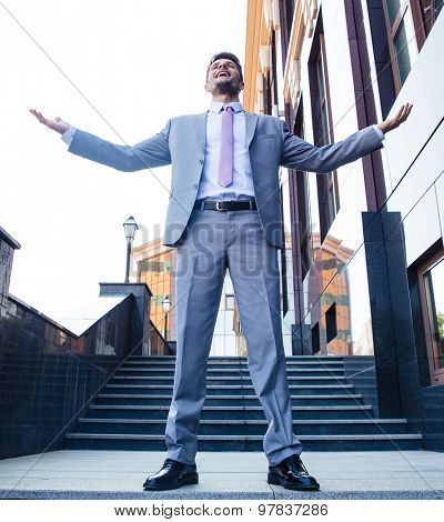 Full length portrait of a excited businessman celebrating his success outdoors