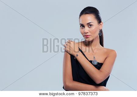 Jewerly concept. Beautiful young woman standing over gray background. Looking at camera