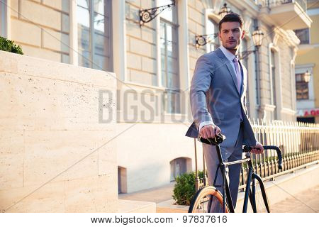 Portrait of a confident businessman standing with bicycle in old town and looking away