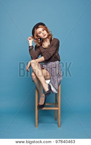 Stylish Woman Sitting On A Chair On A Blue Background