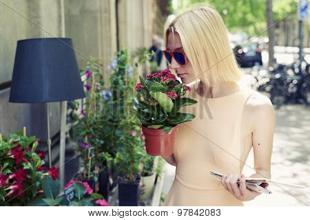 Female tourist with city map holding pot of red flowers at recreation sunny day in summer outdoors