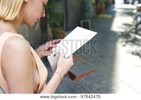 Cropped image young gorgeous woman read empty flyer while holding smartphone in the hands