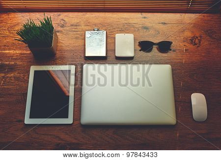 Freelancer needs mock up on wooden table in home interior laptop computer and digital tablet