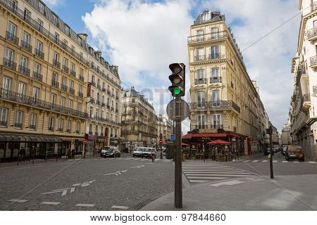 PARIS, FRANCE - MARCH 2, 2015: Street scene in central Paris, showing shops and a street cafe, with typical Parisian architecture.