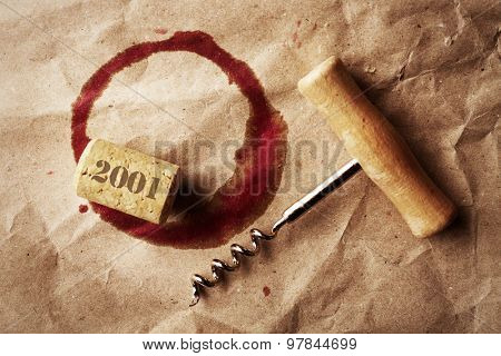 Wine stain, cork and corkscrew on crumpled paper background