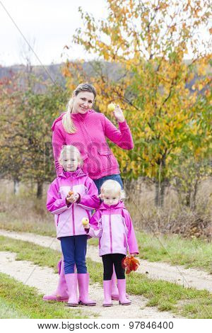mother and her daughters in autumnal nature with apples