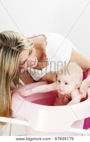 portrait of mother with her baby during bathing