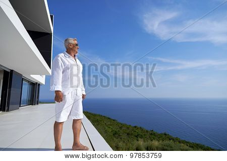 senior man in front of luxury modern home villa