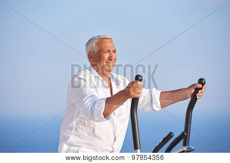 healthy senior man working out on gym treadmill machine at modern home terace with ocean view
