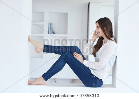happy young woman using cellphone at home and relaxing