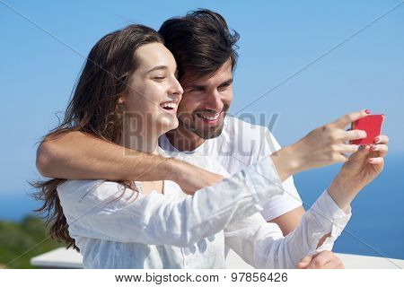happy young couple taking selfie with cell phone