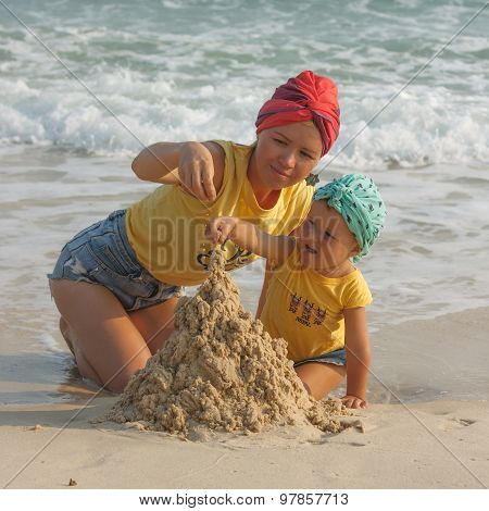 Mother And Daughter Building Sandcastle On The Beach