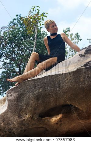 Young Woman Relaxing On Big Picturesque Rock