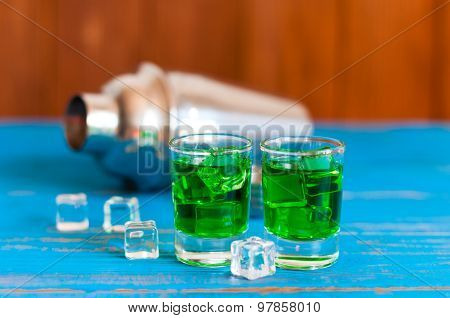 Closeup of two green absinthe alcohol shots with ice cubes and shaker on a light wooden background.