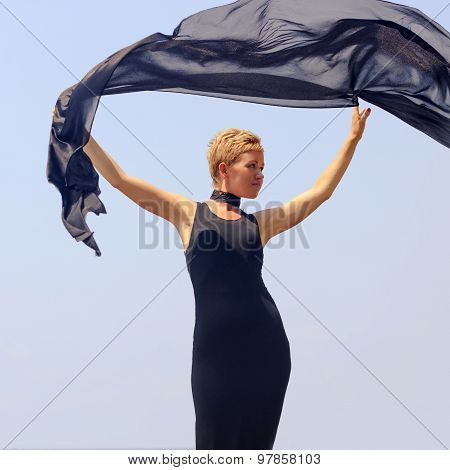 Beautiful Young Woman In Black Evening Dress Holding Black Fabric At Wind At The Seaside