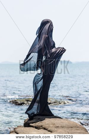 Female  Silhouette Wrapped In Black Fabric Posing At The Rocky Seaside