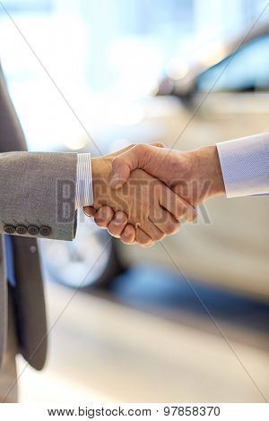 auto business, car sale, deal, gesture and people concept - close up of male handshake in auto show or salon
