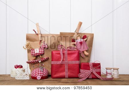 Christmas presents wrapped in paper bags with red white checked ribbon, angel, rocking horse and sewing supplies.