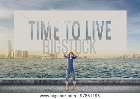 Time to live, words on blank board hold by a young girl in the outdoor.