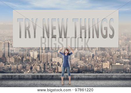 Try new things, words on blank board hold by a young girl in the outdoor.