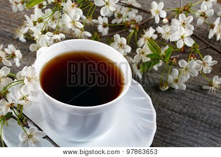 White Cup Of Tea With Flowers Of A Cherry