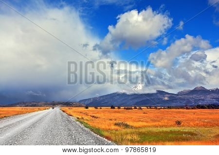On a dirt road on the pampa car rides Strong wind drives the clouds. See the mountains on the horizon