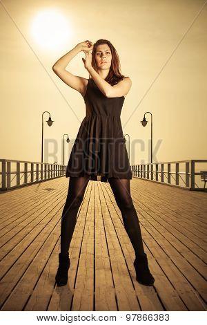 Woman Posing On Pier At Sunrise