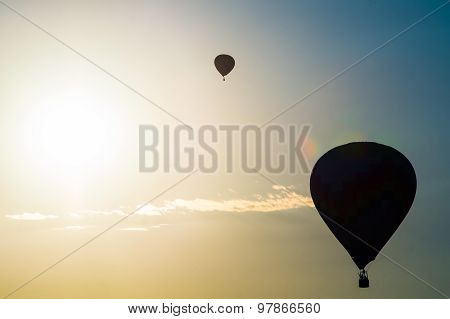 Silhouette of two hot-air balloons by the bright sun