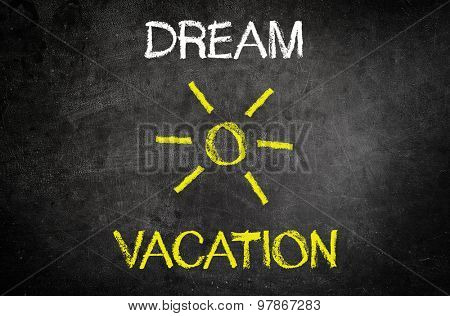 Dream vacation concept with a hand-drawn tropical sun on a chalkboard with the words - Dream Vacation - above and below