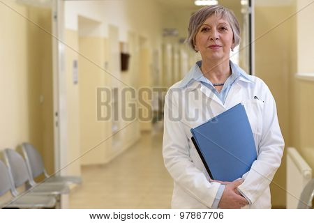 Senior doctor standing in hospital hallway holdings patient files