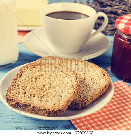 closeup of some toasts in a plate, a cup of coffee, a bottle with milk and a jar of jam on a rustic blue wooden table, with a cross-process effect