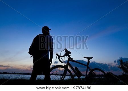 Man Stand On Mountain Bike Silhouette In Sunrise..