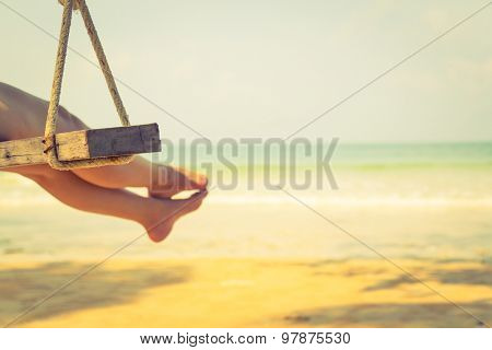 Woman leg  on a swing at tropical sea beach