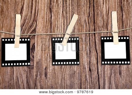 Old Film Blanks Hanging On A Rope Held By Clothespins Over Wood Background
