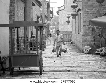 Chinese Man Carrying Bags