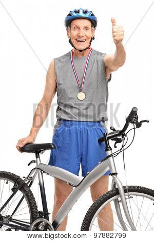 Vertical shot of a senior cyclist posing with a medal and giving a thumb up isolated on white background